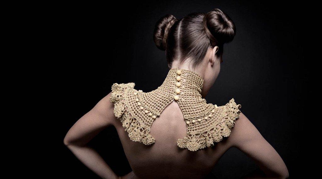 Weibliches Fashionmodel von hinten. Sie trägt lediglich einen künstlerisch gehäkelten Kragen. Im Fotostudio vor schwarz.