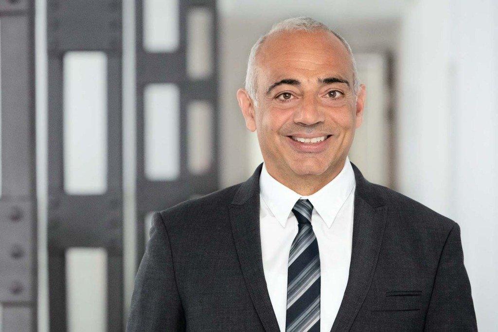 Victor Moftakhar, Vorstand des einigen deutschen Staatsfonds KENFO, steht in dessen Geschäftsräumen in Berlin und trägt Anzug und Krawatte