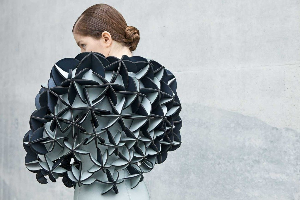 weibliches Fashionmodel mit Neoprenanzug von Alba Prat steht vor einer Betonmauer