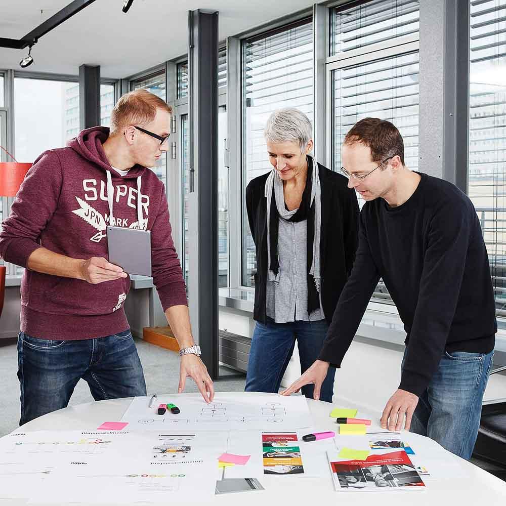 Drei Optivo-Mitarbeiter in einem Kreativmeeting im Berliner Büro
