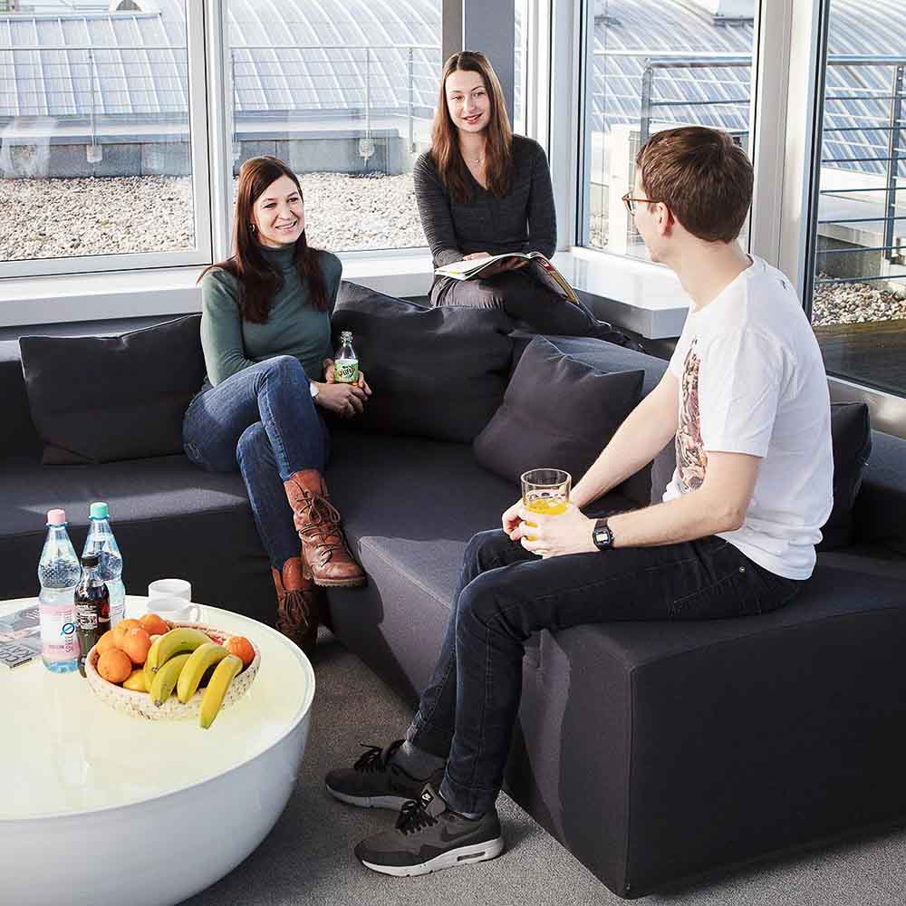Drei Optivo-Mitarbeiter unterhalten sich in einer Bürolounge über den Dächern Berlins