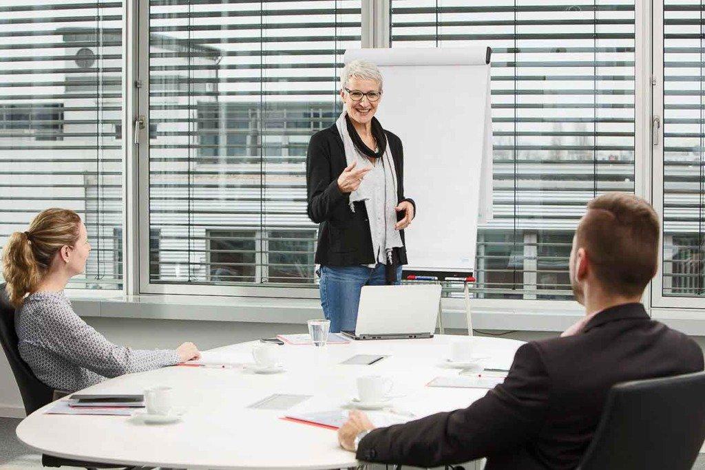 Eine Berliner Optivo-Mitarbeiterin präsentiert etwas vor Kunden am Clipboard