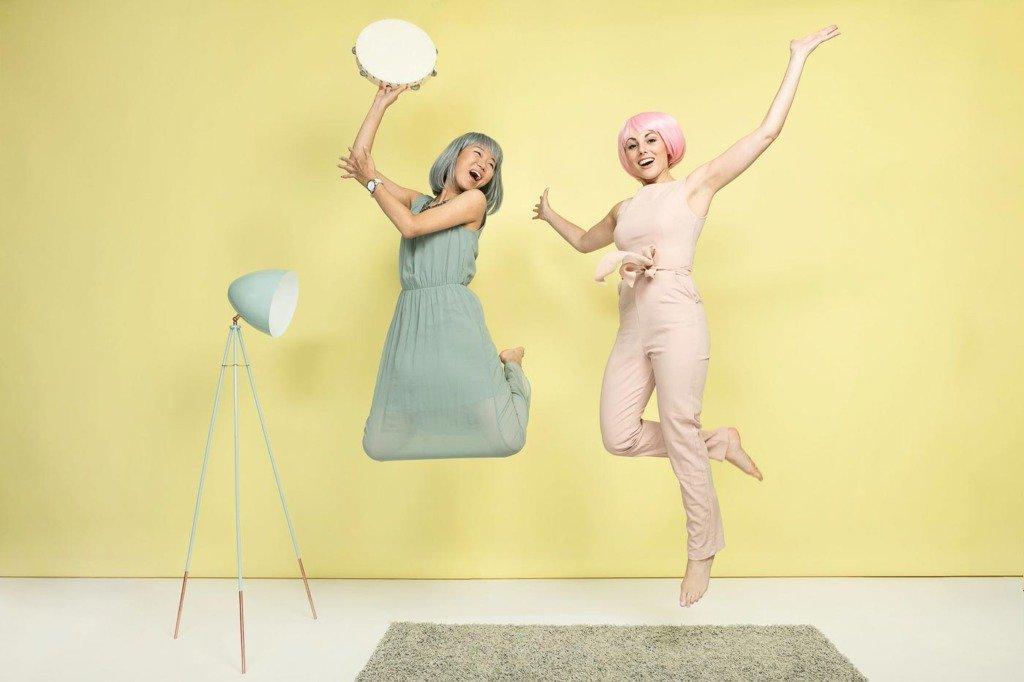 zwei Frauen springen in einem pastellfarbenen Fotostudio in die Luft vor Freude