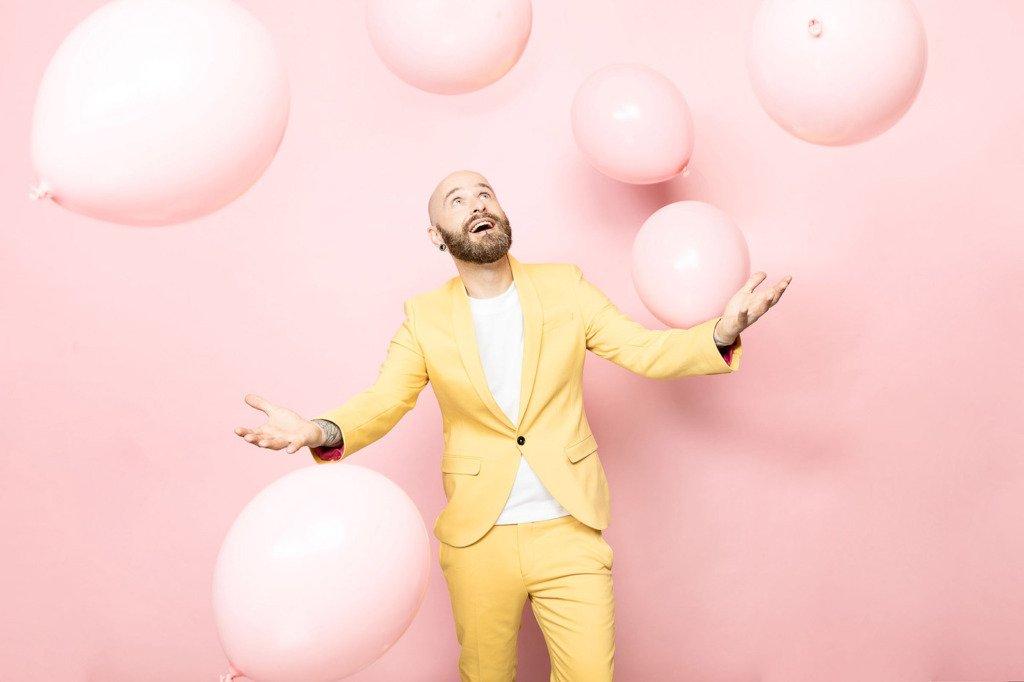 Pastelfoto von Mann im Anzug, der erfreut rosane Luftballons fangen will