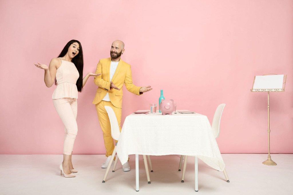 Pärchen in Restaurant-Szene nachgestellt in einem pastellfarbenen Fotostudio