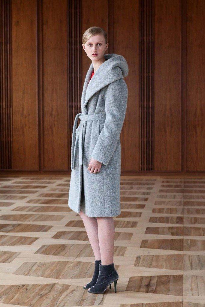 Fashionmodel steht im Kronprinzessinnenpalais Berlin mit einem winterlichen Outfit von Perret Schaad in einem Saal. Für Women's Wear Daily