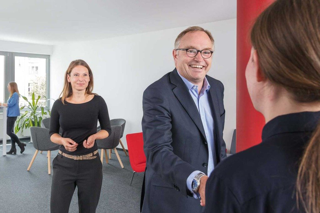 Der Geschäftsführer des Berliner Prognos-Instituts begrüßt eine neue Mitarbeiterin im Empfangsbereich