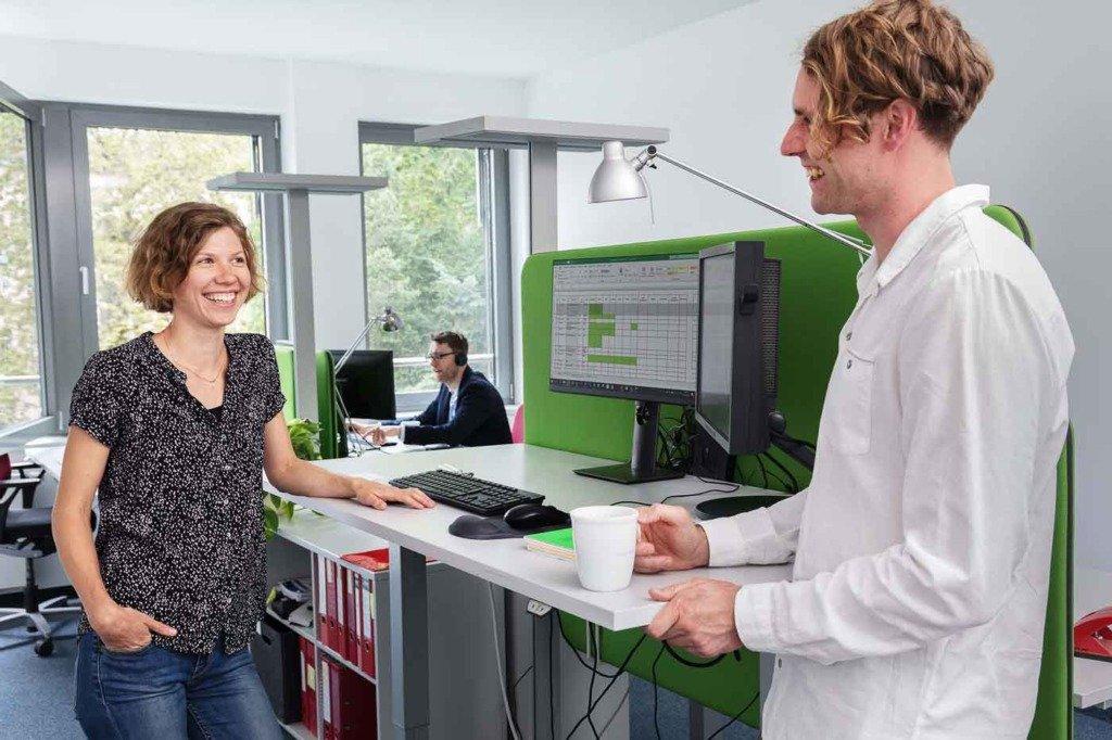 Zwei Zukunftsforscher der Prognos AG unterhalten sich im Stehen am Schreibtisch
