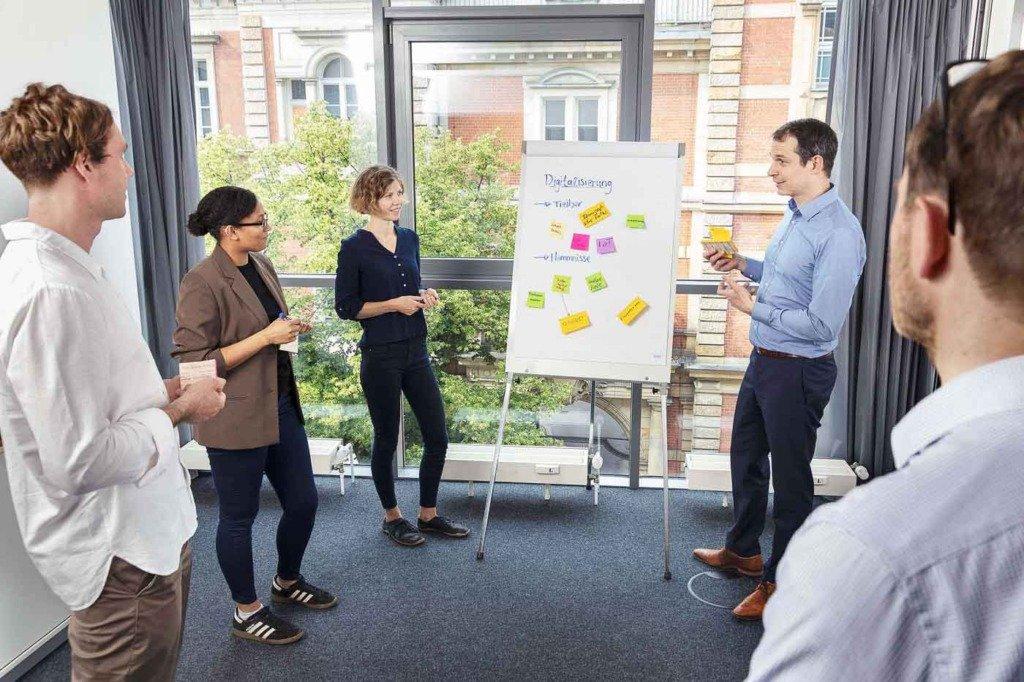 Stehmeeting mit Clipboard von 5 Forschern der Prognos AG im Berliner Büro.