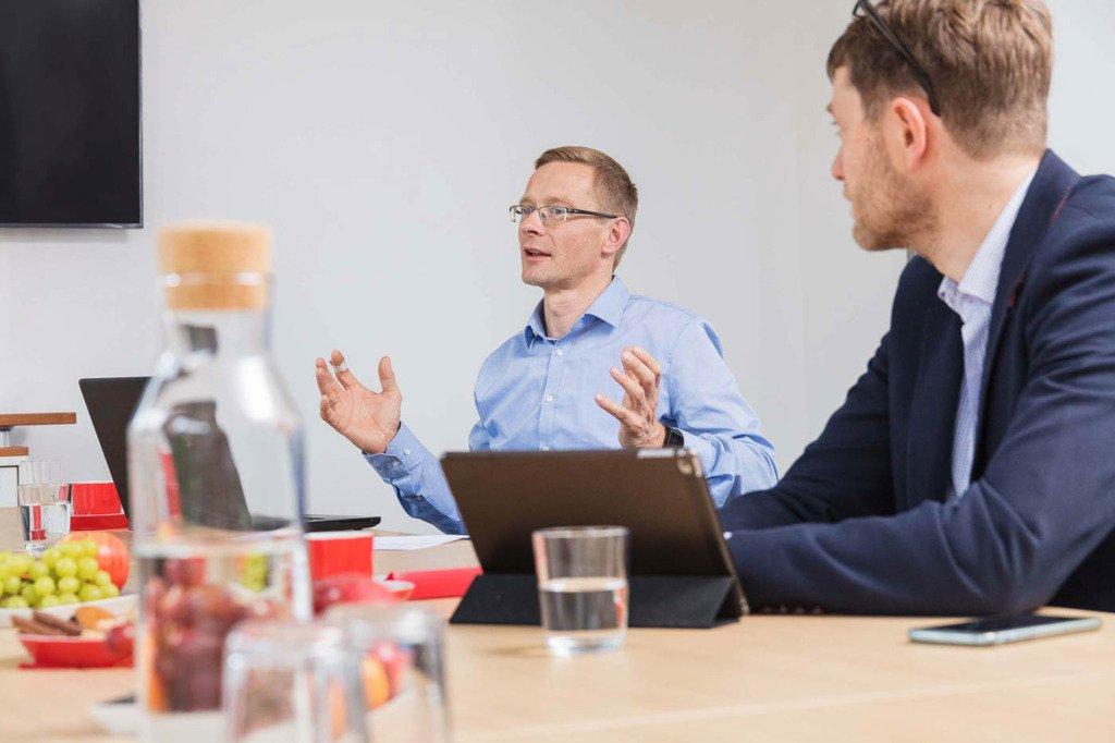 Unternehmensfotos Dynamische Meetingsituation von Forschern der Berliner Prognos AG. Ein Forscher spricht mit Handgeste in den Raum hinein.