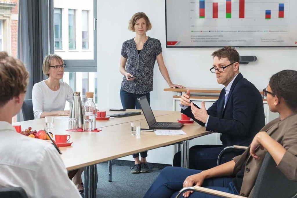 Dynamische Meetingsituation von fünf Forschern der Berliner Prognos AG. Im Hintergrund zeigt ein Großbildschirm eine statistische Grafik. Ein Forscher spricht mit Handgeste in den Raum hinein.