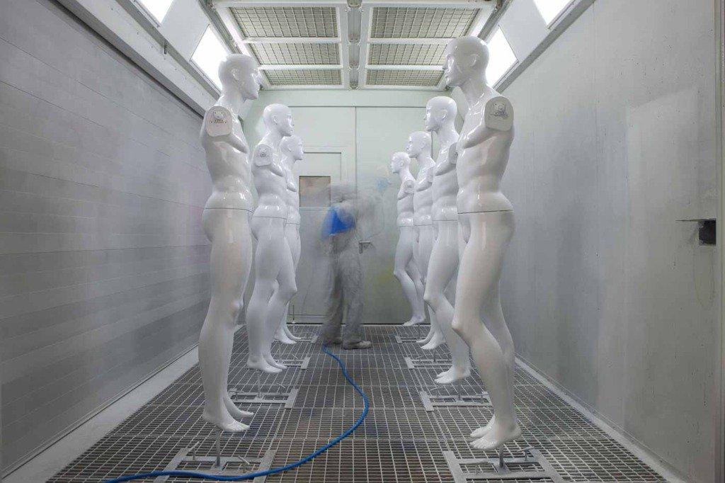 Lackierer in Arbeitskleidung sprüht Lack auf Schaufensterfiguren mit Langzeitbelichtung
