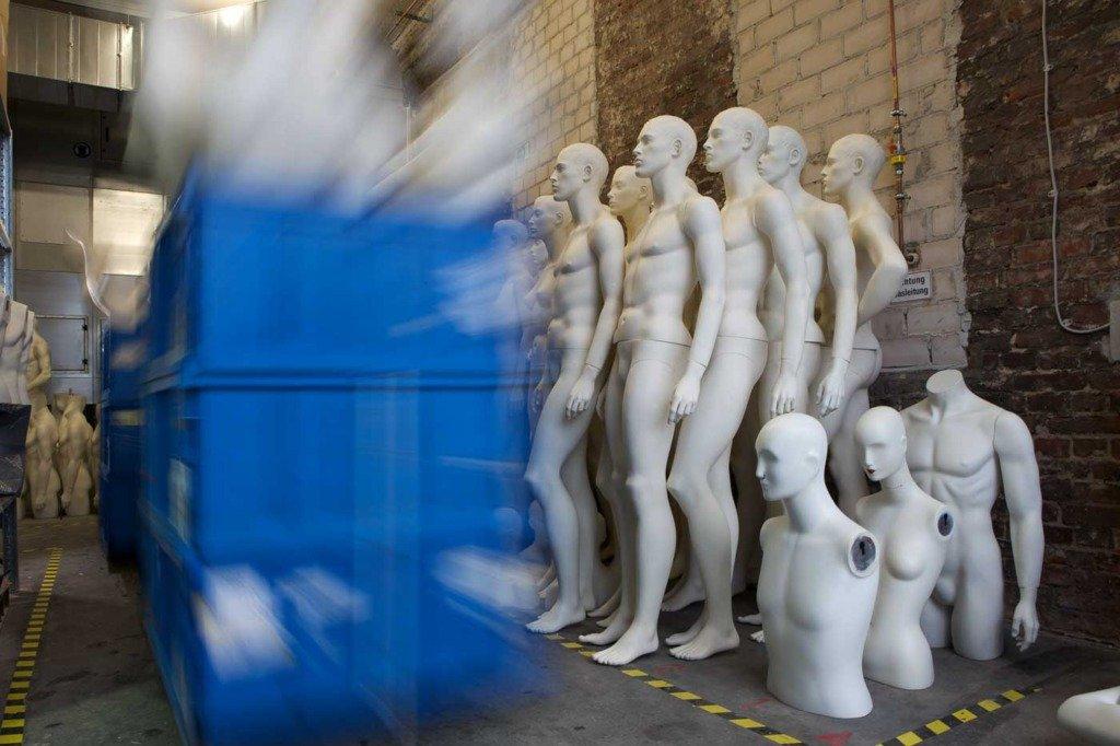 Plastikcontainer mit Schaufensterfiguren werden in eine Lagerhalle gefahren - mit Langzeitbelichtung