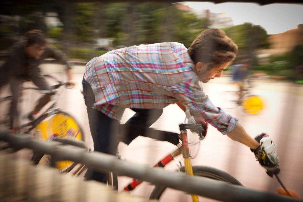 Fahrradpolo-Spieler in einer dynamischen Action-Situation in einem Open-Air-Platz in Barcelona. Die Sportler tragen Kleidung der Marke SPRT.
