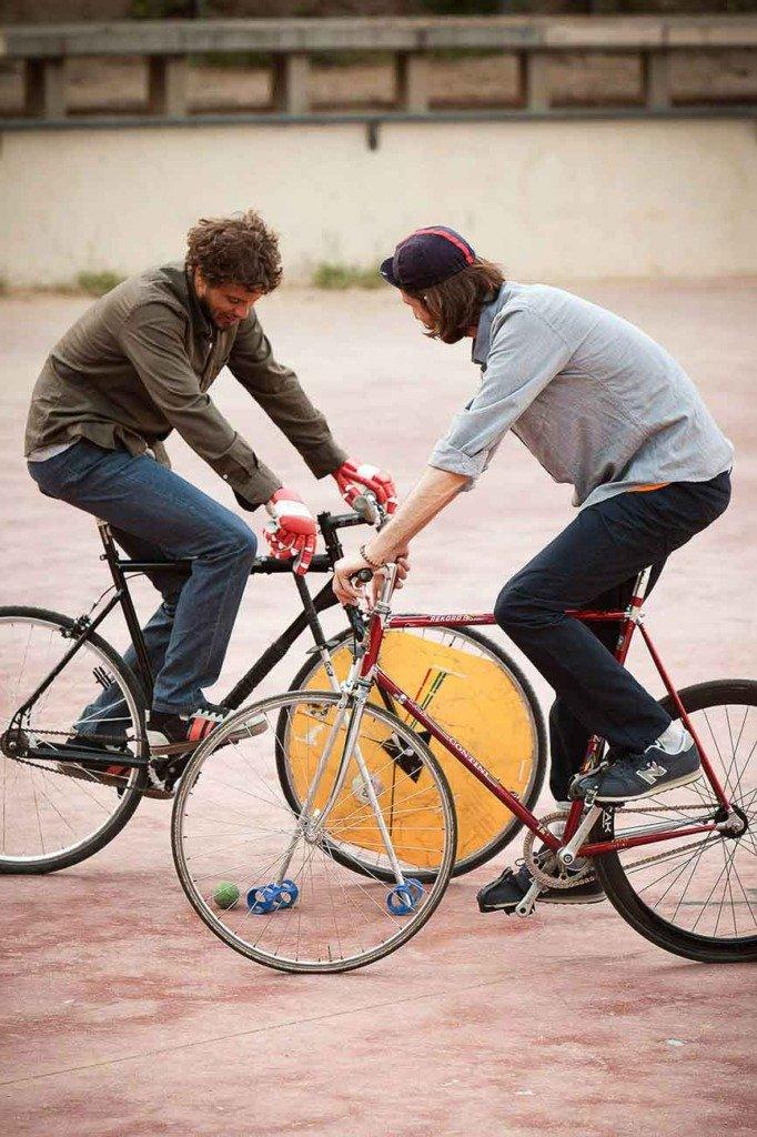 Zwei Fahrradpolo-Spieler in einer Action-Situation in einem Open-Air-Platz in Barcelona. Die Sportler tragen Kleidung der Marke SPRT.