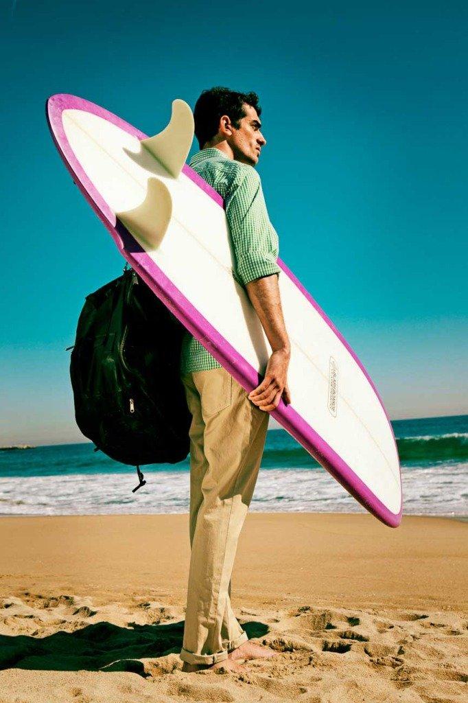 Ein männliches Fashion-Model mit Casual Wear kommt mit Surfbrett am Strand von Barcelona an. Hochkantfoto mit direktem Sonnenlicht