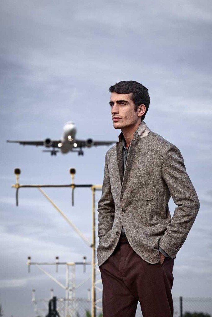 ein männliches brünettes Modell mit Jackett steht in der Nähe des Flughafens mit einem landenden Flugzeug im Hintergrund.
