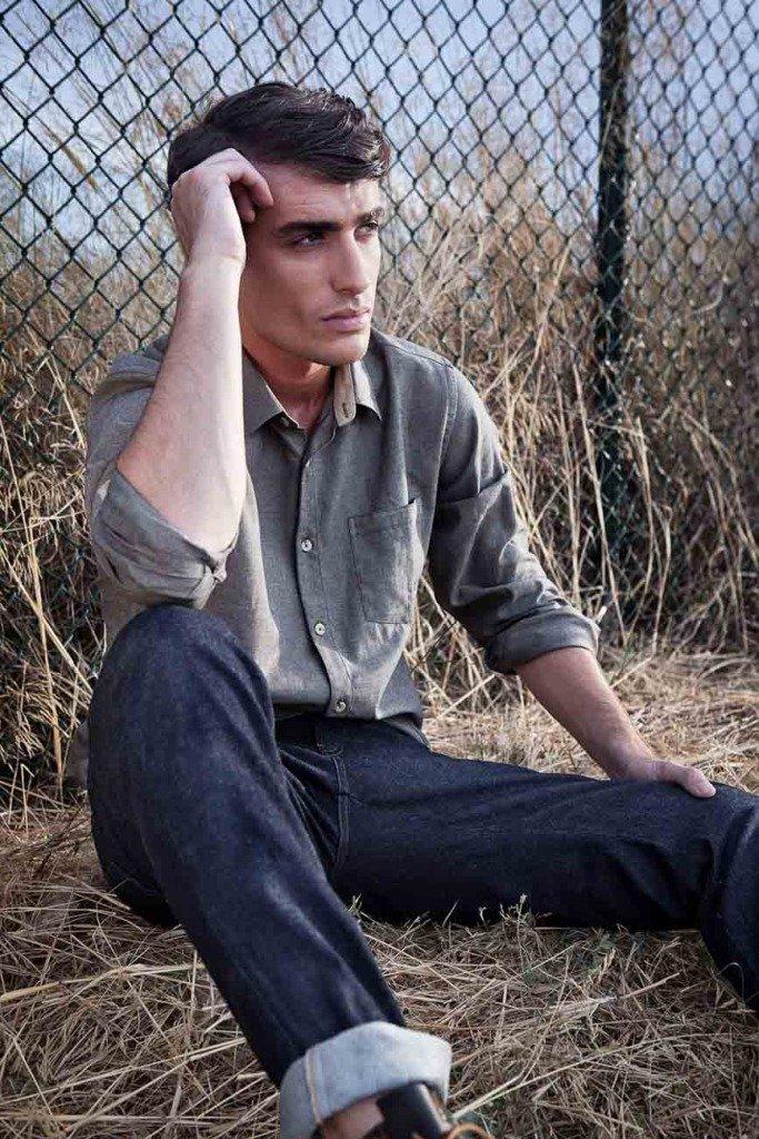 ein männliches brünettes Modell mit Hemd sitzt auf Stroh an einem Maschendrahtzaun