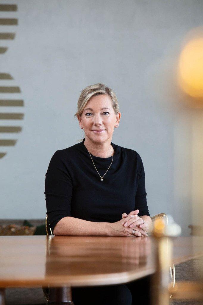 Stephanie Casper, Vorstand von Axel Springer, sitzt an einem Tisch für das Portrait des B2B-Fotografen Matti Hillig