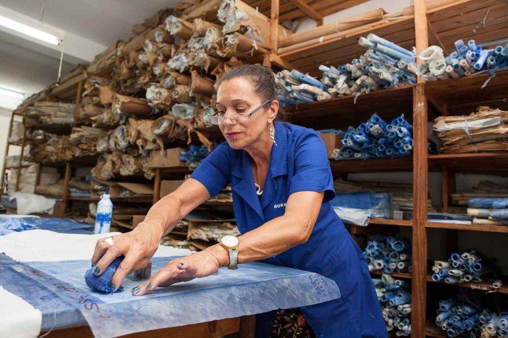 Madeira Stickerei Produktionsprozess Durch Reiben eines Schwamms mit spezieller blauer Tinte wird das Design auf dem Wachspapier durch die Perforationen auf den darunterliegenden Stoff gedrückt