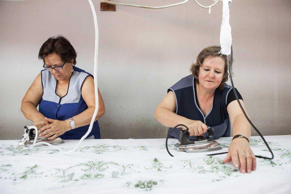 Madeira Stickerei Produktionsprozess, Bügeln nach dem Waschen der Stickerei in der Fabrik, Foto aufgenommen in Funchal, Madeira, Portugal in einer Textilfabrik