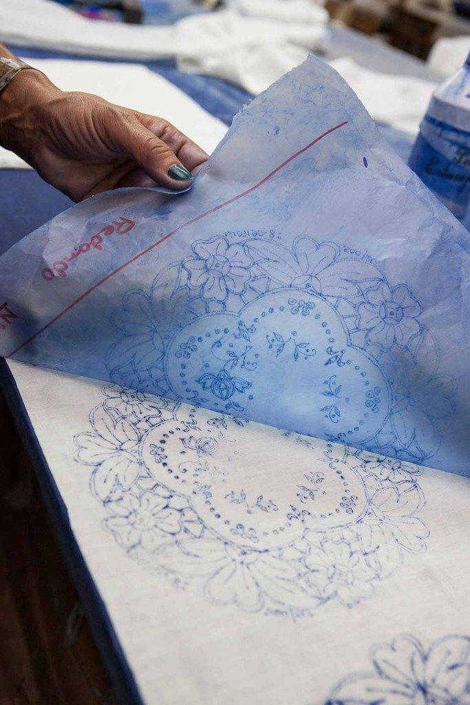Madeira Stickerei Produktionsprozess: Durch Reiben eines Schwamms mit spezieller blauer Tinte wird das Design auf dem Wachspapier durch die Perforationen auf den darunter liegenden Stoff gemalt