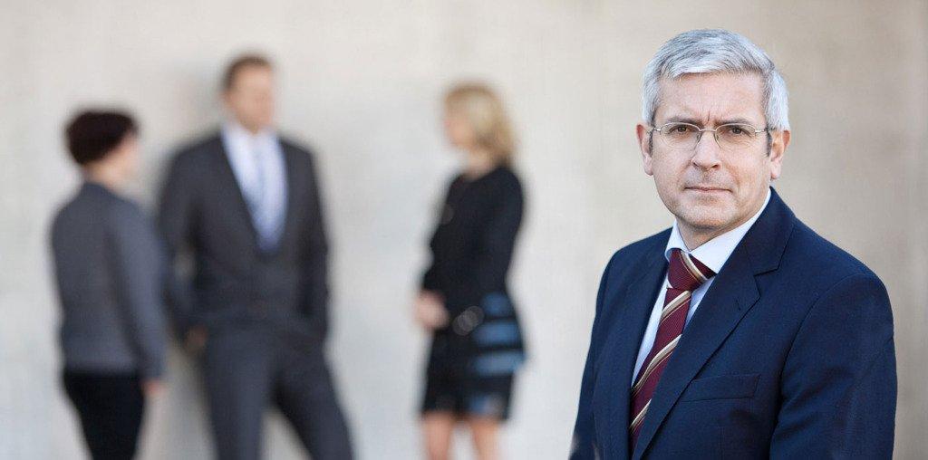 Businessportrait vom Baurechtsanwalt Gerald Süchting. Im Hintergrund unscharf sieht man seine Partner der Kanzlei Süchting Partner