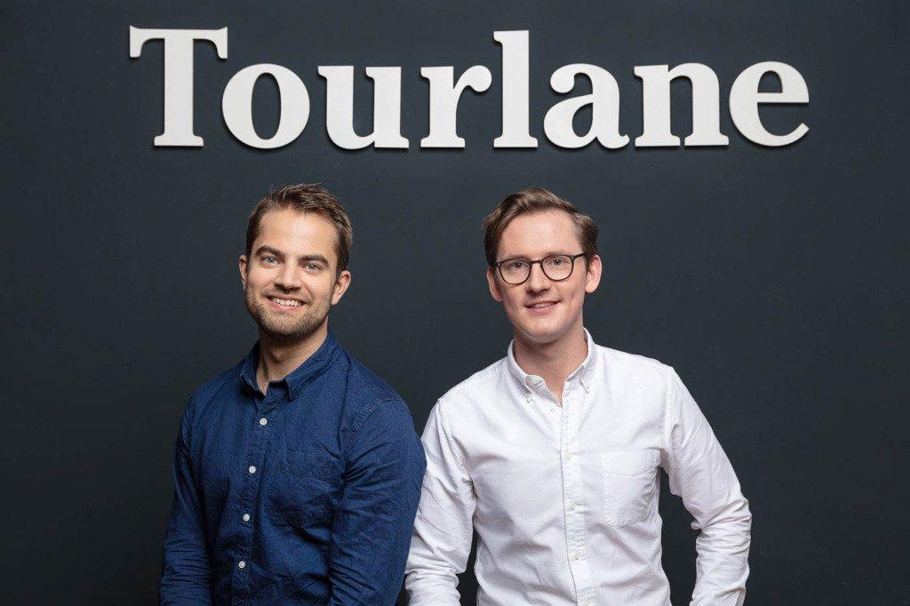 Die beiden Gründer und CEOs des Berliner Startups Tourlane, Julian Stiefel und Julian Weselek, sitzen im Casual-Look vor dem Firmenlogo