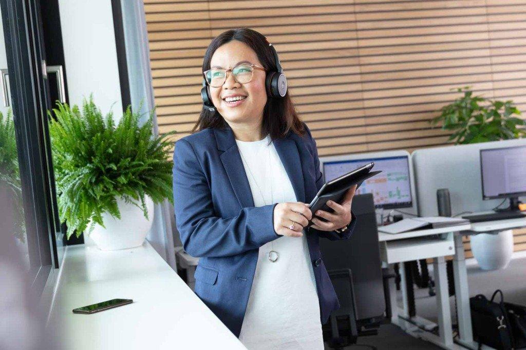 Eine Exekutiv-Assistentin von Verivox telefoniert mit Headset und Ipad im Büro