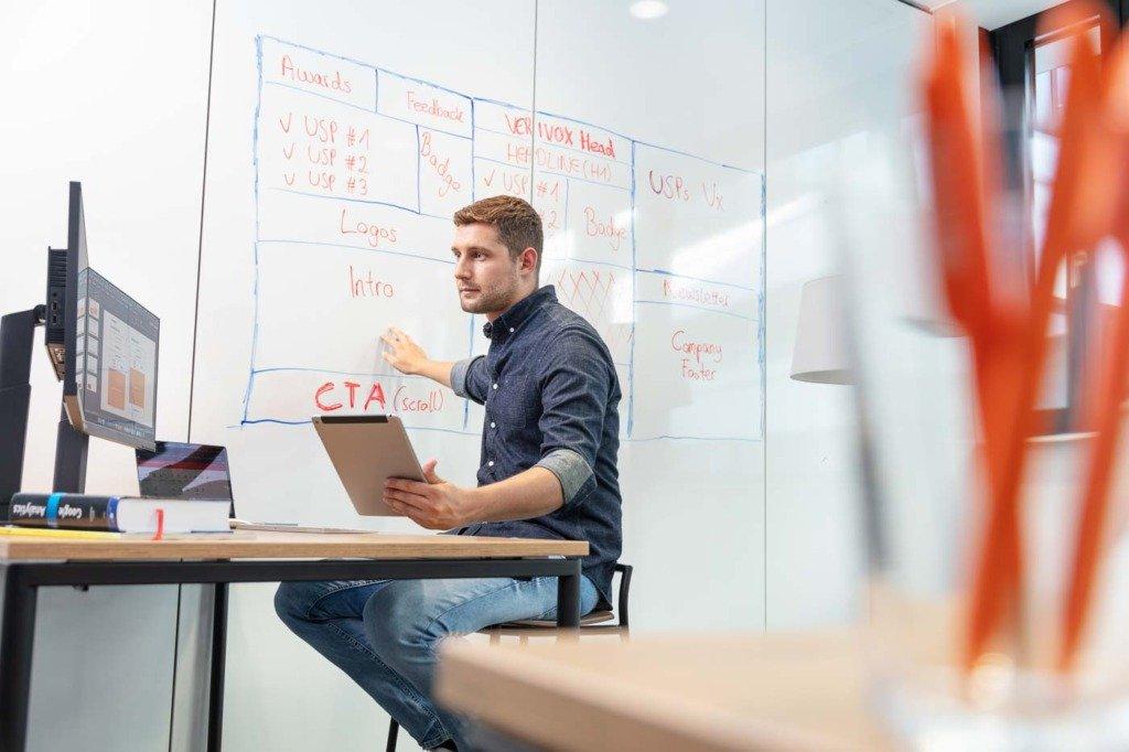 Eine Online-Marketing-Experte von Verivox gleicht an einem Schreibtisch eine Whiteboard-Webseiten-Architektur mit Informationen am Computermonitor ab.