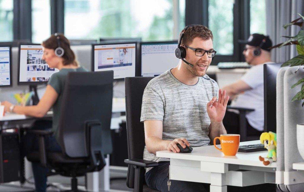 Ein Mitarbeiter des Verivox Callcenters ist mit Headset im Kundengespräch. Freudig erklärt er technische Details. Im Hintergrund sitzen weitere Customer Care Agenten an Monitoren
