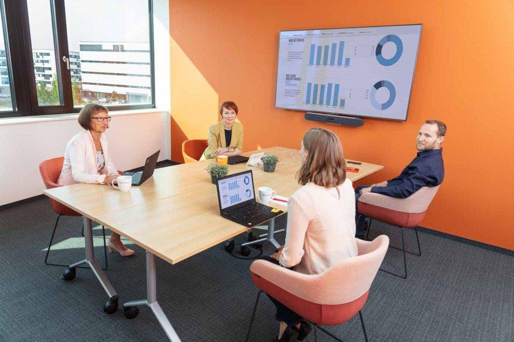 Teammeeting der Finanzabteilung von Verivox mit Groß-Screen. Die casual chic gekleideten vier Controller beraten über eine Chart, welches am Wand-Screen zu sehen ist.