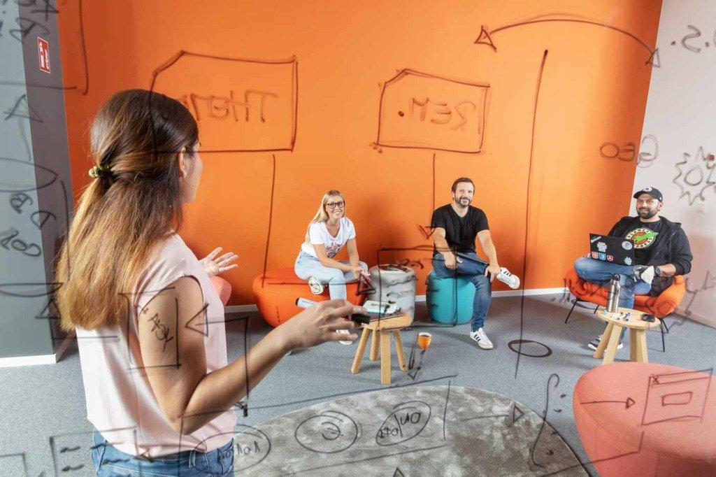 Programmierer von Verivox diskutieren eine Code-Architektur in einer Büro-Lounge