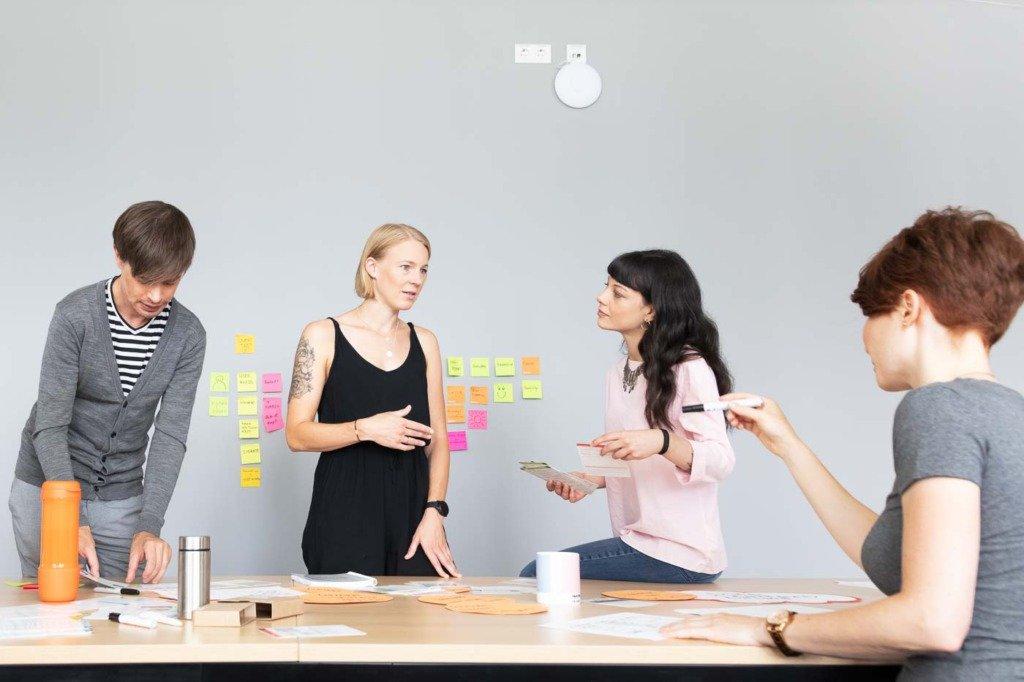 UX-Designer des Unternehmens Verivox besprechen Designs in einem Kreativmeeting. An der Wand kleben bunte Post-Its. Die Teilnehmer sind leger gekleidet