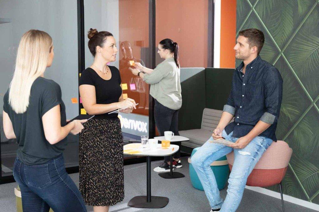 Kreativbrainstorming des Marketings von Verivox. Im Hintergrund klebt eine Mitarbeiterin Post-Its. Die Location ist eine modern eingerichtete, informelle Sitzlounge