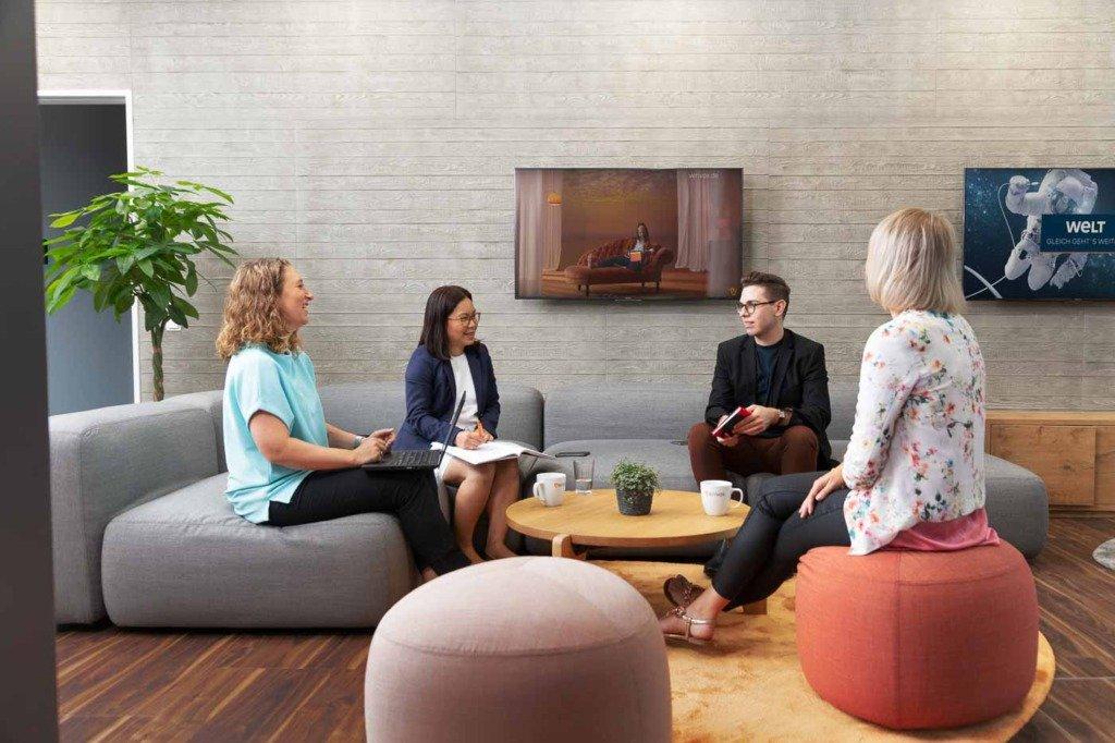 Das Verivox-Assistenz-Team bespricht die wöchentlichen Aufgaben in der wohnlichen Empfangslounge des neuen Heidelberger Hauptquartiers von Verivox.