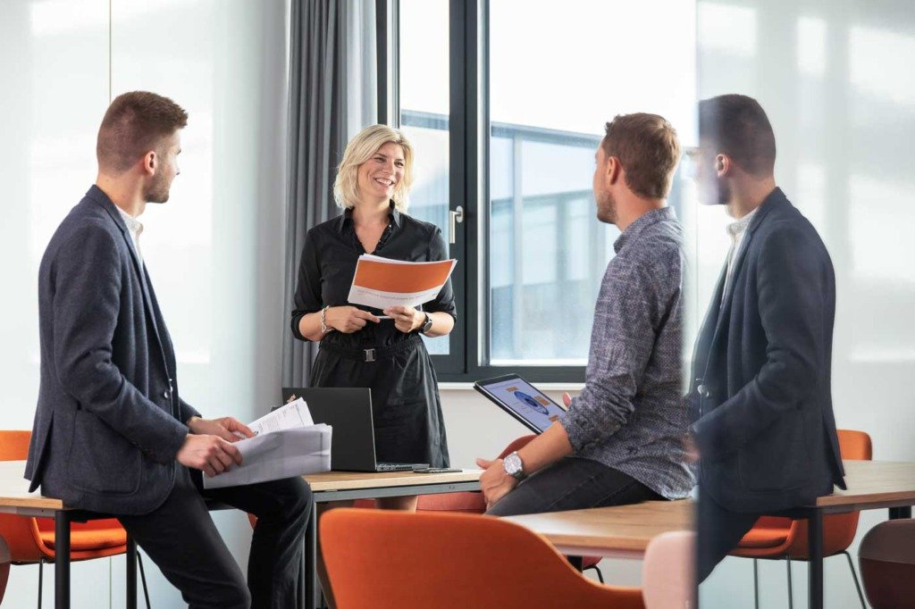 Das Strategie-Team von Verivox bereitet in einem Meetingraum eine wichtige Präsentation vor. Die drei Consultants sind casual chic gekleidet und sitzen auf Tischen eines modernen Besprechungsraums