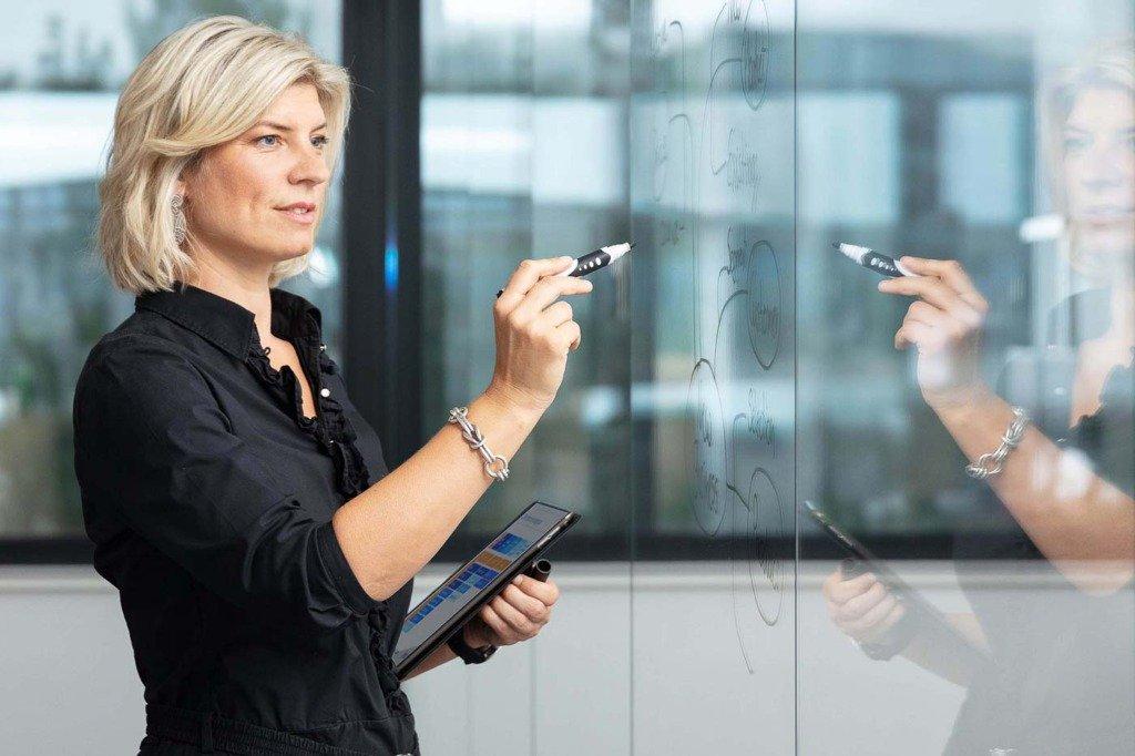 Eine junge Managerin scribbelt in einem modernen Bürogebäude eine Planung an eine Glaswand. In ihrer linken Hand hält sie einen Tablett-Computer. Ihre Kleidung ist casual chic