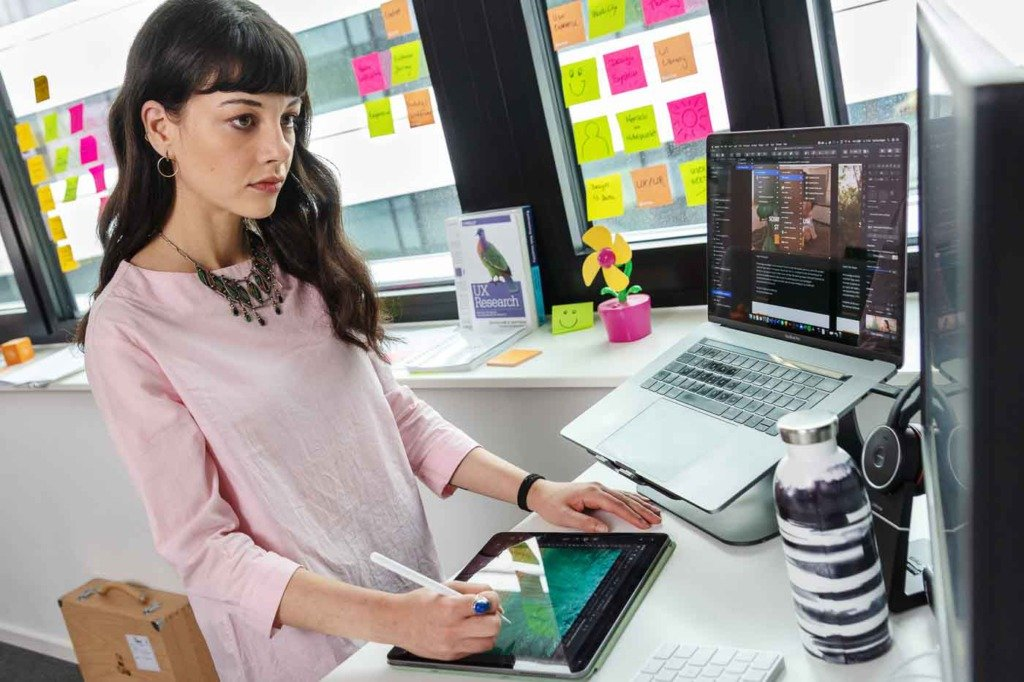 Eine junge UX-Designerin arbeitet mit einem Tablet und Desktop-Computer in Photoshop im Büro von Verivox. Ihre Kleidung ist casual, das Büro wirkt kreativ. Am Fenster kleben viele bunte Post-its