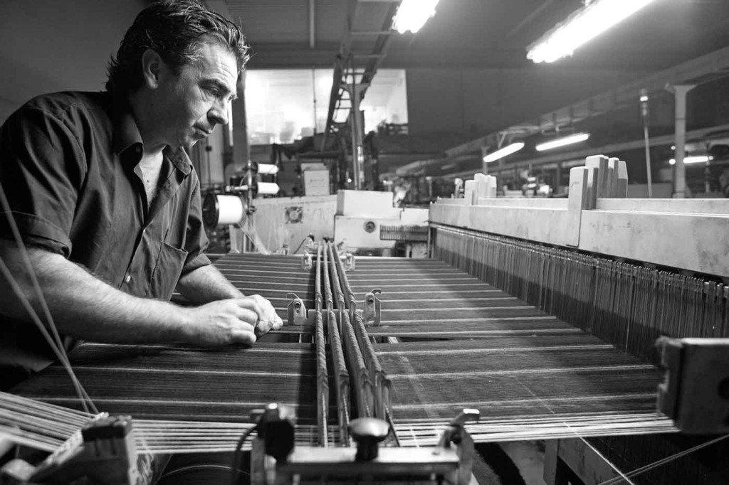 Ein Arbeiter arbeitet an einer Webmaschine. Herstellung von Anzugstoffen in einer Fabrik in Sabadell, Spanien