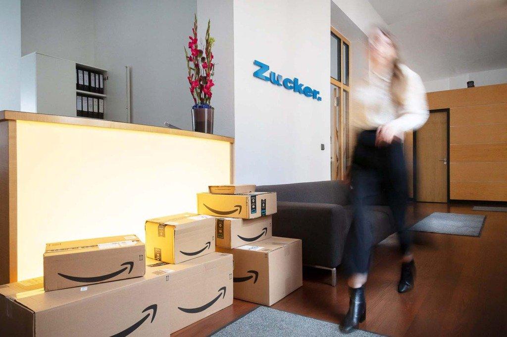 Eine Mitarbeiterin der Berliner PR-Agentur Zucker läuft im Eingangsbereich an zahlreichen Postpaketen vorbei