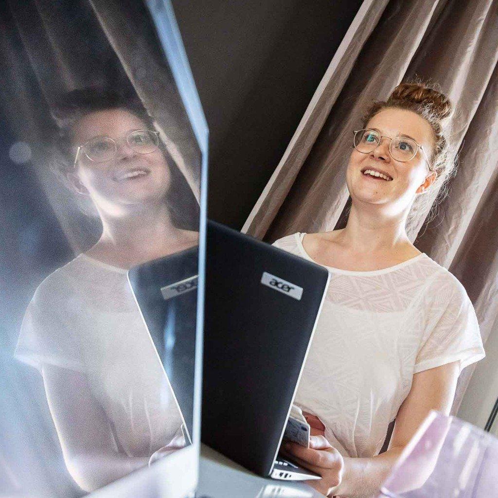 Dokumentarische Aufnahme einer Frau die sich im Monitor spiegelt - während eines Meetings. Aus einer Fotoserie über die Arbei