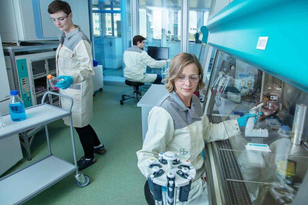 Drei Laboranten arbeiten mit Reagenzgläsern in einem Labor eines Berliner Pharmaunternehmens
