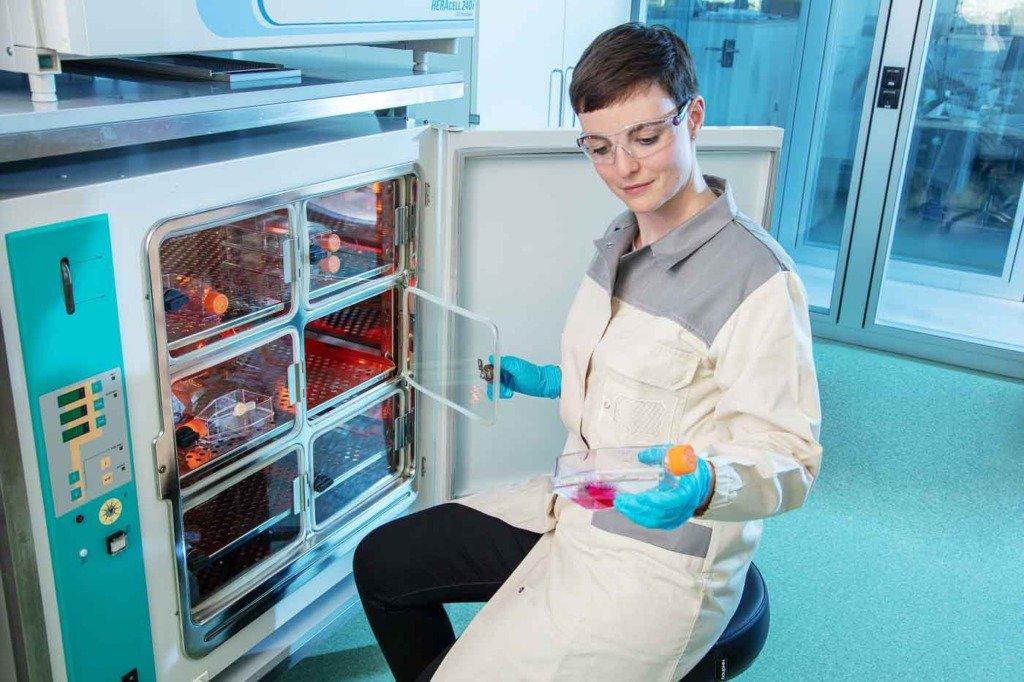 Eine Mikrobiologie-Laborantin eines Pharmaunternehmens öffnet einen Wärmeschrank und holt ein Reagenzglas mit Serum heraus.