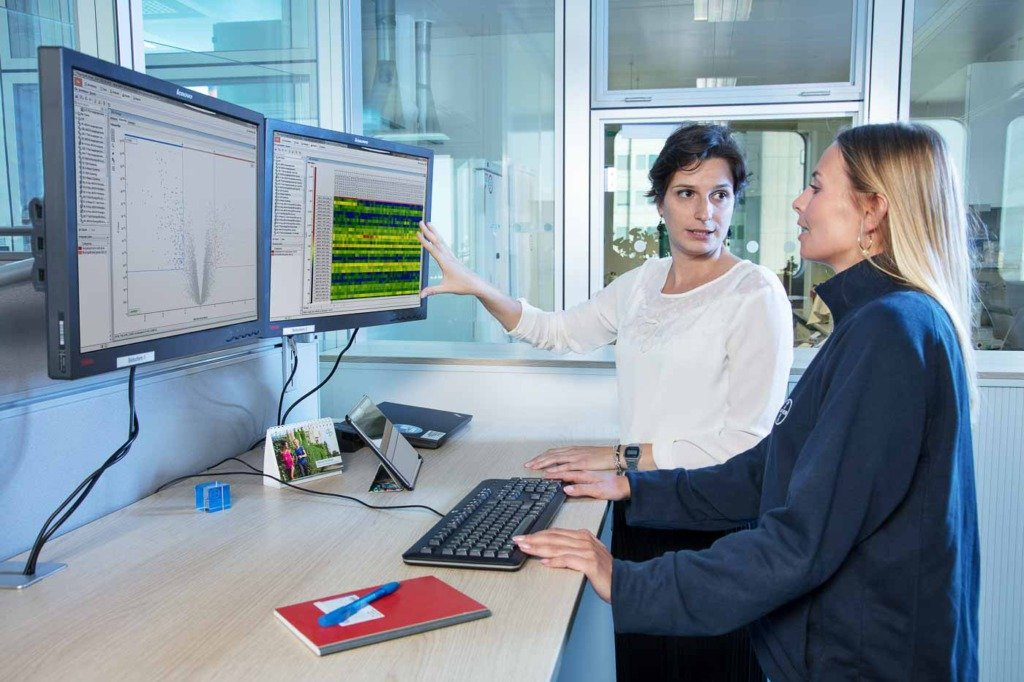 Zwei Wissenschaftlerinnen diskutieren Mikrobiologie-Daten an großen Bildschirmen
