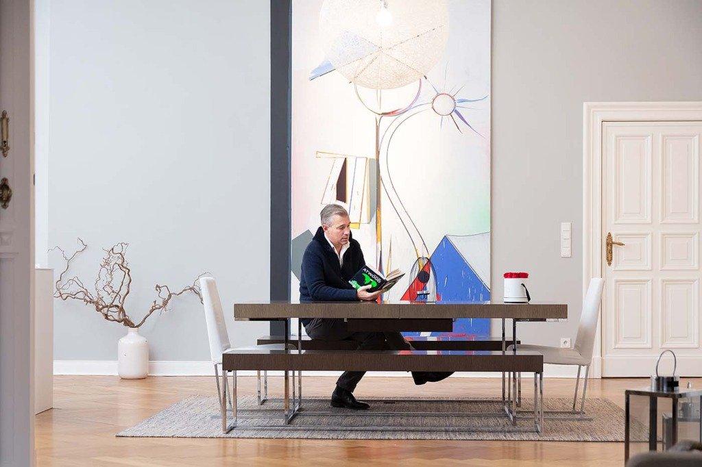 Finanzinvestor Christian Schneider Sickert liest ein Buch in seiner Berliner Wohnunng. Homestory für Citywire Deutschland