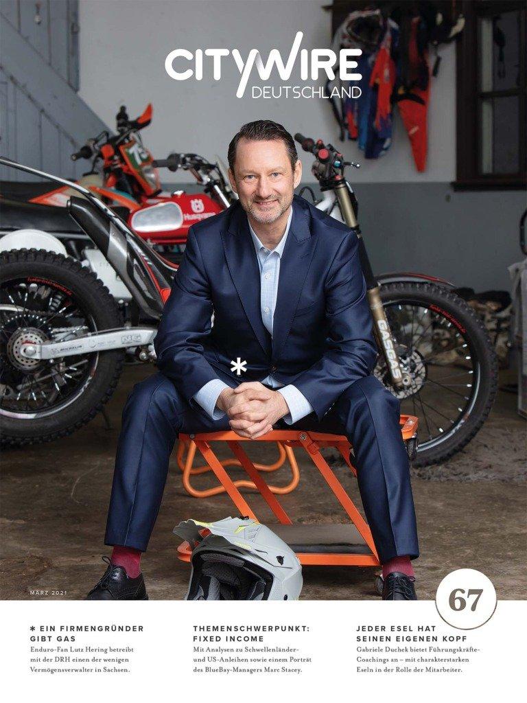 Fondmanager Lutz Hering sitzt im Anzug vor seinen Motocross-Motorrädern